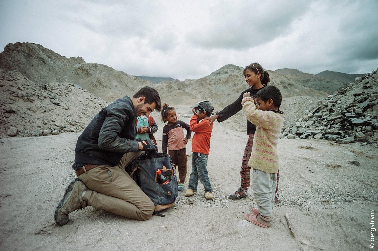 Niklas Huppmann (SHADES OF LOVE) verteilt Sonnenbrillen an Kinder.